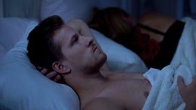 Задумчивый человек думая о разводе вечером, жена спать, неправильные решения жизни стоковые фотографии rf