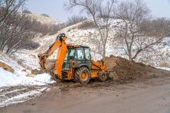 Затяжелитель Backhoe против снежных холма и деревьев стоковое изображение