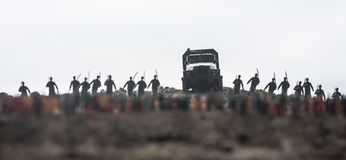 Захваченный враждебной концепцией Военные силуэты и толпа на предпосылке неба тумана войны Солдаты и бронированные транспортные с стоковое изображение