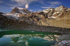 Заход солнца в горах Небольшое озеро, даже в зиме, температура воды + 30 градусов Долина гейзеров над взглядом стоковая фотография rf