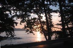 Заход солнца над морем Andaman в Пхукете, Таиланде Взгляд захода солнца через деревья на береге стоковое изображение