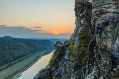 Заход солнца на реке Эльбе с горной породой и деревьями на утесе и лесах на реке стоковая фотография