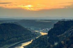 Заход солнца на реке Эльбе с деревней и древесинах в осени и некоторой горной породе стоковое фото rf