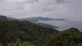 Зеленая гора на острове в пасмурной дождливой погоде, верхняя часть горы спрятана под белыми облаками сток-видео