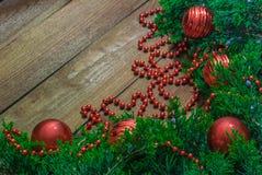 Зеленые ветви с ягодами обильно украшенными с игрушками для того чтобы украсить рождественскую елку на деревянном столе стоковые изображения