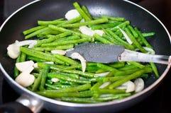 Зеленые фасоли с луком и чесноком готовыми для варить в сковороде Близкий поднимающий вверх взгляд зеленых фасолей на сковороде стоковая фотография rf