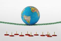 Земля планеты балансируя на веревочке над штырями нажима - концепции планеты и экологических рисков здоровья стоковое изображение rf
