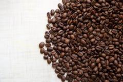 Зерна черного кофе лежат на светлом деревянном столе, фоновом изображении установьте текст стоковые изображения rf