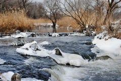 Зимний ручей. The winter stream passing into small falls Stock Image