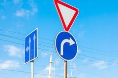 Знак который показывает дорогу и поворот только справедливо к предпосылке гениального голубого неба стоковое изображение rf