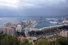 Здания, порт, залив, корабли и горы против облачного неба Драматическое небо над городом красивейший взгляд стоковые фотографии rf