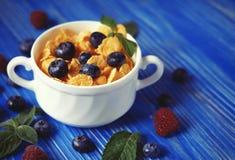 Здоровая еда, еда и концепция диеты - корнфлексы с полениками и голубиками ягод на голубой деревянной предпосылке стоковое фото