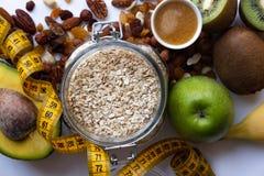 Здоровая еда и концепция фитнеса Свежие фрукты, гайки и хлопья на белой предпосылке стоковые изображения rf