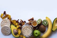 Здоровая овсяная каша завтрака с изюминками и гайками Миндалины, мед, яблоко, авокадо, банан на белой предпосылке таблицы скопиру стоковые фотографии rf