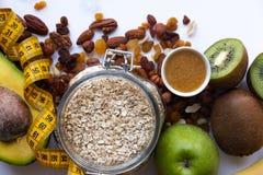 Здоровые ingrediens завтрака Домодельный granola в открытом стеклянном опарнике, меде, гайках, плодах, желтой лент-майне на белой стоковое фото rf