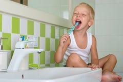 Зубы малого мальчика чистя щеткой в ванной комнате Начало нового дня стоковое изображение