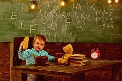 Зрачок ест еду на деревянном столе Маленький зрачок наслаждается перерыв на ланч в классе Меню школы для зрачка Сегодня зрачок стоковое фото