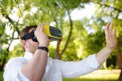 Зрелый человек используя шлемофон виртуальной реальности на открытом воздухе VR, стекла VR, увеличенный опыт реальности стоковое изображение
