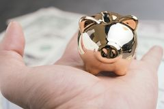 Золотая копилка в руке с предпосылкой денег банкнот доллара США использующ как бюджет, сбережения или вклад контроля стоковое изображение rf