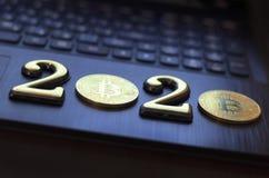 золотое bitcoin оно лежит на клавиатуре темного цвета Надпись 2020 Тонизировать стоковые изображения rf