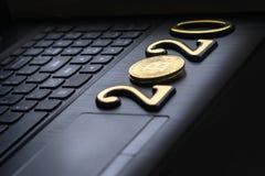 золотое bitcoin оно лежит на клавиатуре темного цвета Надпись 2020 Тонизировать стоковое изображение rf