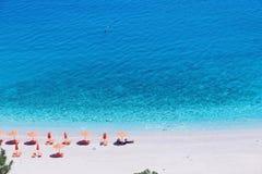 Зонтики и пляж Apella стульев сверху, остров Karpathos, Греция стоковые фото