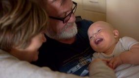 Игра бабушки и деда с их маленьким внуком, нежно щекочет его и забавляет, ребенк смеется весело видеоматериал