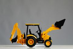 Игрушка трактора Backhoe, серая предпосылка стоковые изображения rf