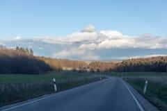 Изгибать дорогу между полями и деревьями в Германии Langgöns в зиме стоковое изображение
