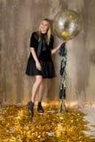 Изумительная милая дама празднуя день рождения Нового Года, представляющ в предпосылке блеска золота и бросая красочный confetti  стоковое фото