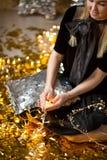 Изумительная милая дама празднуя день рождения Нового Года, представляющ в предпосылке блеска золота и бросая красочный confetti  стоковая фотография rf