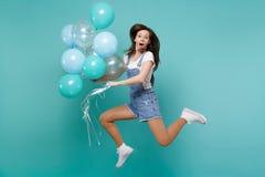 Изумленная молодая женщина в одеждах джинсовой ткани держа рот открытый, скакать высокий, праздновать, держа красочные воздушные  стоковые изображения rf
