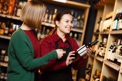 Изображение 2 женщин с бутылкой вина в магазине на предпосылке полок стоковое изображение