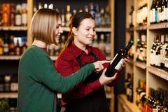 Изображение 2 женщин с бутылкой вина в магазине на предпосылке полок стоковое изображение rf