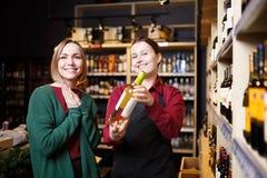 Изображение молодых женщин с бутылкой вина в руках в магазине стоковое фото rf