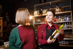 Изображение молодых женщин с бутылкой вина в руке стоковая фотография