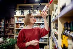 Изображение молодой женщины с бутылкой вина в руке стоковые фото
