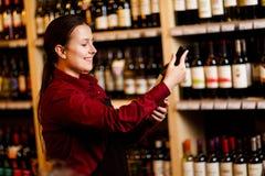 Изображение молодой женщины с бутылкой в ее руках в винном магазине стоковое фото rf