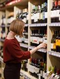 Изображение на стороне женщины с бутылкой вина на запачканной предпосылке полок с бутылками стоковое фото