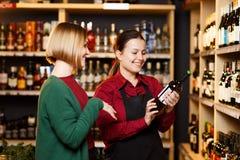 Изображение на стороне 2 женщин с бутылкой вина в магазине на предпосылке полок стоковые фотографии rf