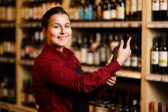 Изображение счастливой женщины с бутылкой в ее руках в винном магазине стоковое изображение