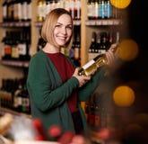 Изображение счастливой женщины с бутылкой в ее руках на запачканной предпосылке полок с бутылками вина стоковое фото rf