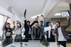 Изображение счастливой команды дела празднуя победу в офисе Успешная команда дела бросает куски бумаги в современном офисе стоковое фото