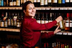 Изображение усмехаясь женщины с бутылкой в ее руках в винном магазине стоковое изображение