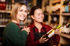 Изображение 2 усмехаясь женщин с бутылкой вина в магазине на предпосылке полок стоковые изображения
