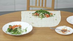 Ингредиенты для варить shawarma на кухонном столе дома Пита, овощи и зеленый лук с соусом и видеоматериал