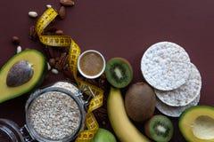 Ингредиенты для здоровых плодов завтрака, овсяной каши, гаек, авокадоа, хрустящих хлебов, на коричневой предпосылке стоковое изображение rf