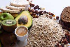 Ингредиенты для здоровых плодов завтрака, овсяной каши, гаек, авокадоа, хрустящих хлебов, на белой предпосылке стоковое фото rf