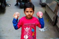 Индийский ребенк готовый для того чтобы поломать баллон воды на людях стоковые фото