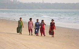 Индия, GOA, 22-ое января 2018 Группа в составе индийские женщины в ярких и красочных сари идет вдоль seashore или пляжа индийско стоковая фотография rf